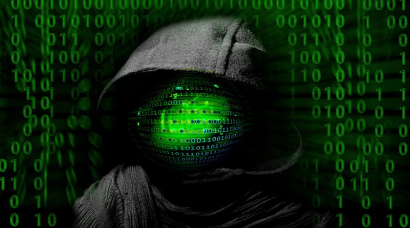 hooded hacker against backdrop of code