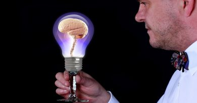 man holding a lightbulb with a brain inside it