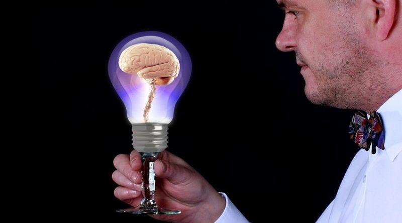 man holding a lightbulb with a brain inside it