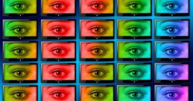 Multiple monitor screens, each displaying an eyeball