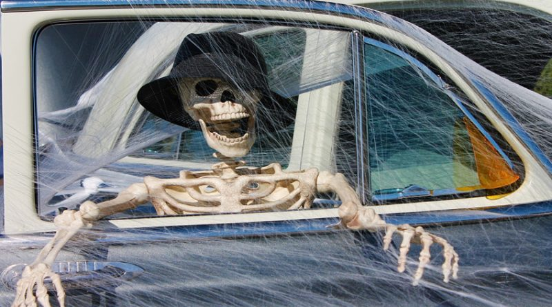 Skeleton wearing a hat sitting in a car