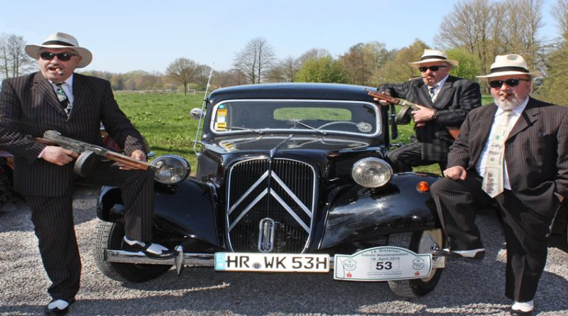 Gangsters stood in front of vintage car
