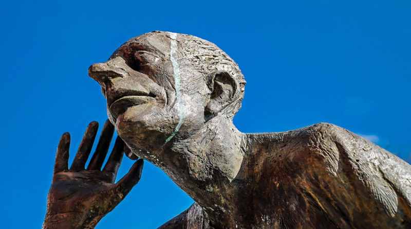 Sculpture of man listening with hand cupped to ear