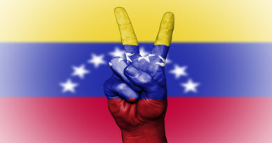 Peace hand symbol against backdrop of Venezuelan f;lag