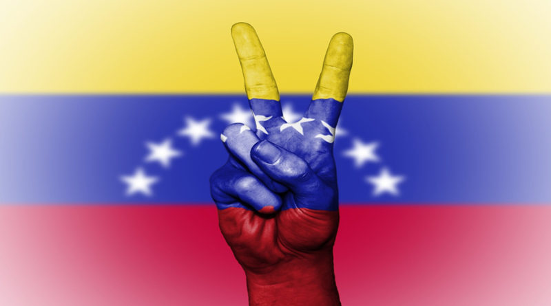 Peace hand symbol against backdrop of Venezuelan f;lag