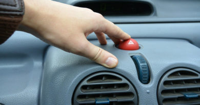 Finger pressing red hazard switch on car dashboard