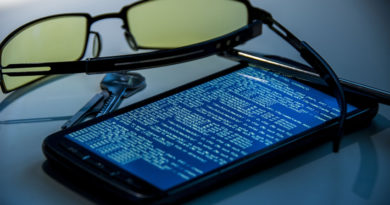 Glasses and keys next to a smartphone with code on screen