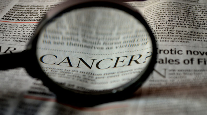 The word cancer viewed in a newspaper under a magnifying glass