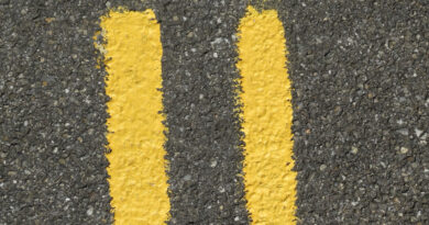 Number eleven painted in yellow on a tarmac road surface